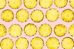 Risiedere affettato dei pezzi dell'ananas nel modello sulle sedere rosa-chiaro isolate fotografia stock libera da diritti