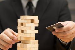Risiko des Kreditkartekonzeptes Geschäftsmann, der den hölzernen Block wählt Lizenzfreie Stockfotografie