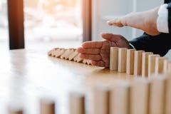 Risikokonzept mit der Hand des Geschäftsmannstoppens und -schutzes der Domino-Effekt stockbild