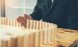 Risikokonzept mit der Hand des Geschäftsmannstoppens und -schutzes der Domino-Effekt lizenzfreie stockfotos