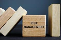 Risikomanagement-Konzept Hölzerner Würfel und Ziegelsteine mit Domino-Effekt lizenzfreies stockbild