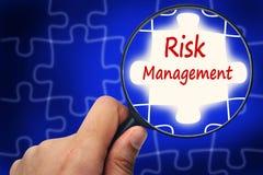 Risikomanagementwort Vergrößerungsglas und Puzzlespiele Lizenzfreie Stockbilder