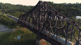 Rising Aerial Establishing Shot of Coal Train on Railroad Bridge. 9276 A dynamic rising aerial establishing shot of a cargo trail traveling on a railroad bridge stock footage