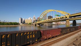 Rising Aerial View of Cargo Train in Pittsburgh. 8470 PITTSBURGH - Circa May, 2017 - A rising aerial view of the skyline of Pittsburgh, PA while a cargo train stock footage