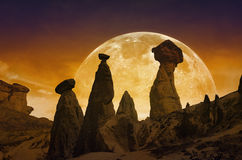 Rising bloody red full moon, silhouettes of mushroom rocks in Ca. Scenic mystical background - rising bloody red full moon, silhouettes of mushroom rocks on red Stock Image
