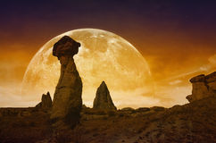 Rising bloody red full moon, silhouettes of mushroom rocks Stock Images
