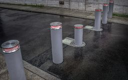 Rising bollards. Retractable lifting bollards with warning light to enable or block traffic Royalty Free Stock Image
