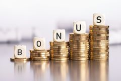 Rising bonus. Rising stacks of coins with the word bonus royalty free stock photo