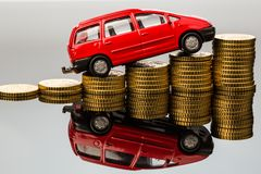 Rising car costs. car on coins. In a car you have rising costs by fuel, insurance, parking fees and tolls stock photography