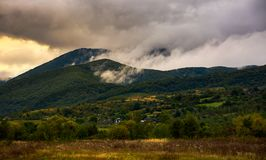 Rising clouds in mountainous countryside. At menacing sunrise. village at the foot of the mountain. rainy weather Royalty Free Stock Photos