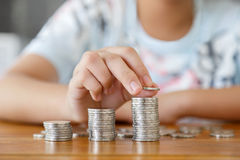 Rising coins. A girl putting coins to rising stack of coins on wooden table stock photos