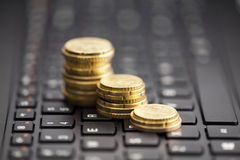 Rising coins on keyboard Royalty Free Stock Images