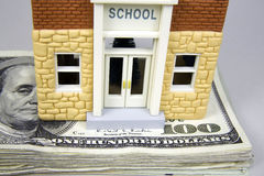 Rising Cost of Education. School house atop a stack of one hundred dollar bills Stock Photos