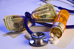 Rising cost of healtcare and medicine. Stethoscope tied around money and pills spilling out of prescription bottle Stock Photo