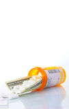 Rising cost of healthcare. A twenty dollar bill in a bottle of pills, with white tablets spilling out across the bill. Illustrating the high cost of healthcare Royalty Free Stock Photos