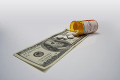 RISING COST OF HEALTHCARE 3. Photo symbolizing the rising cost of health care featuring US currency, pills, and generic pill bottle on grey background Stock Photo