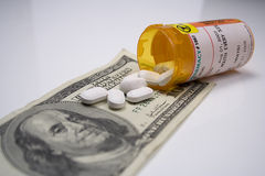 RISING COST OF HEALTHCARE. Photo symbolizing the rising cost of health care featuring US currency, pills, and generic pill bottle on grey background Royalty Free Stock Photos