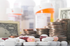 Rising cost of healthcare. Medication and money piled high, illustrating the increasing cost of health care Royalty Free Stock Photos