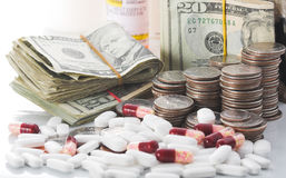 Rising cost of healthcare. Medication and money piled high, illustrating the increasing cost of health care Royalty Free Stock Photo