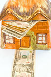 Rising cost of property. An abstract image of an old cottage with a ten dollar bill forming the path to the door and more bills protruding from the roof Stock Photo