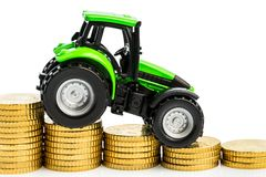 Rising costs in agriculture. Farmers in agriculture have to reckon with rising costs. higher preies in fodder, fertilizer and plants. tractor with coins Royalty Free Stock Images