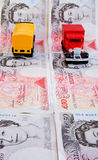 Rising costs of transport. A close up image with selective focus of a red lorry and yellow van on a mock road created with fifty pound notes. A concept image of Royalty Free Stock Photography