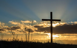 Rising Cross Sun. Sun behind a cross and a cloud too Stock Photo