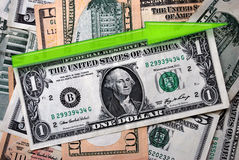 Rising Dollar. One american dollar and green arrow indicates growth on a pile of another american banknotes Royalty Free Stock Photography