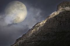 Rising full moon over the rocky summit. Artistic concept of the full moon rising over the Pindus mountain range in north-west Greece royalty free stock photos