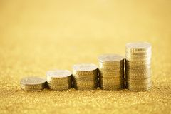 Rising golden coins. On golden glitter background royalty free stock image