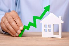 Rising house prices. Man is holding green arrow up in his hand and house. On the table stock photos