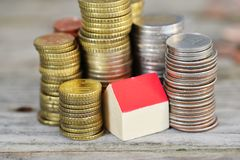 Rising houses prices concept with miniature wooden house and piles of coins on wooden background. High houses prices concept with miniature wooden house and stock photo