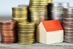 Rising houses prices concept with miniature wooden house and piles of coins on wooden background royalty free stock images