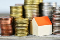 Rising houses prices concept with miniature wooden house and piles of coins on wooden background stock photos