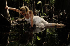 Rising from the Mire. Girl grasping a tree trying to get out of a muddy bog Royalty Free Stock Images