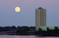 Rising Moon. Full moon rising over the power plant at dusk Stock Image