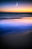 The Rising Moon. A rising moon on a calm ocean with blue sand dunes and a colorful sunset royalty free stock photo