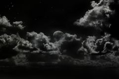 Rising moon. Rising full moon under dramatic light cloud in a sky full of stars,space for text stock images