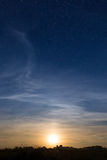 Rising moon in dark blue sky with stars Royalty Free Stock Image