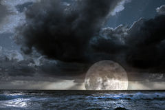 Rising moon in ocean Royalty Free Stock Image