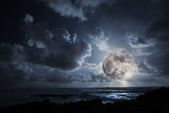 Rising moon in ocean Stock Photography