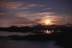 Rising moon over Atlantic Ocean Road in Norway. Rising moon over Atlantic Ocean Road - Atlanterhavsveien, in Norway. Winter night over this famous road royalty free stock images