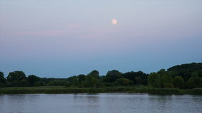 Rising moon at sunset stock footage