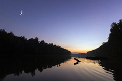 Rising new moon at sunset, over river. Crescent moon Clear sky. Stock Photography