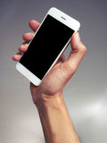 Rising phone. Close-up of a hand rising a phone stock photography