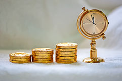 Rising pile of gold coins with a clock stock photography