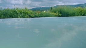 Rising from a Pool in Tuscany. Medium wide handheld high dynamic range shallow depth of field slow motion point of view shot rising in a swimming pool midst the stock footage