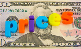 Rising prices: US Dollars. A macro concept image of rising prices shown on a fifty dollar bill. Lower case colorful letters making the word ' prices ' sloping royalty free stock image