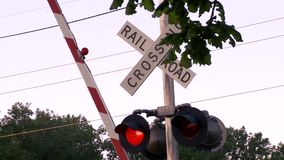 Rising rail road, crossing sign. After a train traveled past, the cross guard started moving up at this railroad crossing sign. Shot in 1080p on the Sony Ex-3 stock video footage