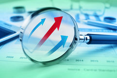 Rising red and blue arrow on magnifying glass over graph Royalty Free Stock Photography
